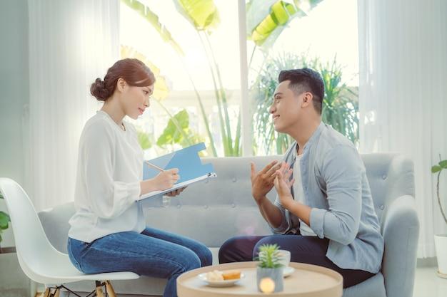 彼女のオフィスで彼女のクライアントに相談している若いアジアの女性心理学者。
