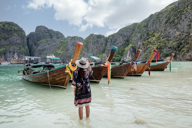 Young asian female raising arm with happiness on coastline with wooden boat in maya bay at phi phi island, krabi