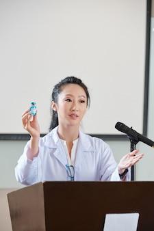 젊은 아시아 여성 과학자가 컨퍼런스에서 연설하고 그녀의 팀이 어떻게 새로운 백신을 연구하고 있는지 설명합니다.
