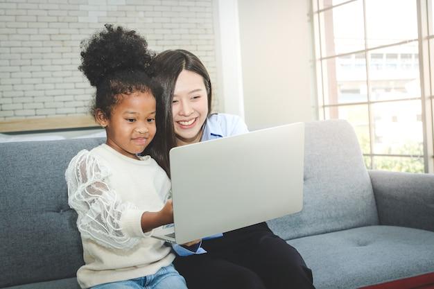 집에서 아프리카 계 미국인 여성 학생들에게 과외 젊은 아시아 여성 교사