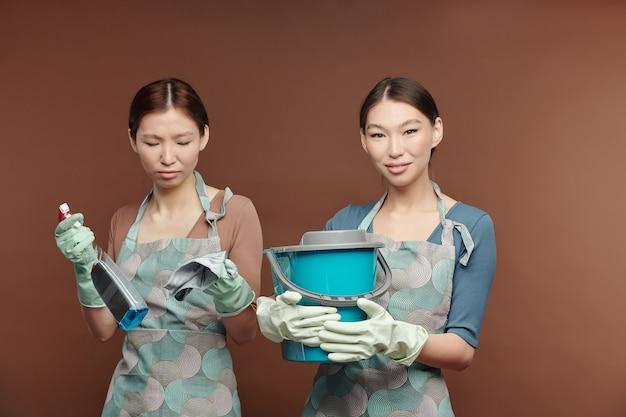床を掃除し、家具からほこりを拭き取りに行く間、洗剤、ダスター、バケツを保持しているエプロンと手袋の若いアジアの女性の双子
