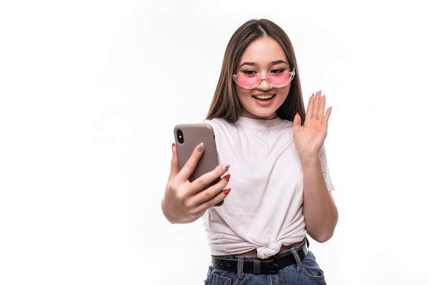 흰 벽에 고립 된 그녀의 휴대 전화를 사용하는 젊은 아시아 여성