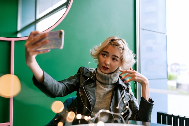 Young asian female with blonde hair making selfie with fairy lights