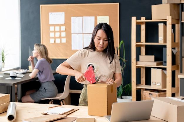 Молодая азиатская женщина-работник офиса интернет-магазина или кладовой упаковывает одну из картонных коробок с заказом, заклеивая ее клейкой лентой