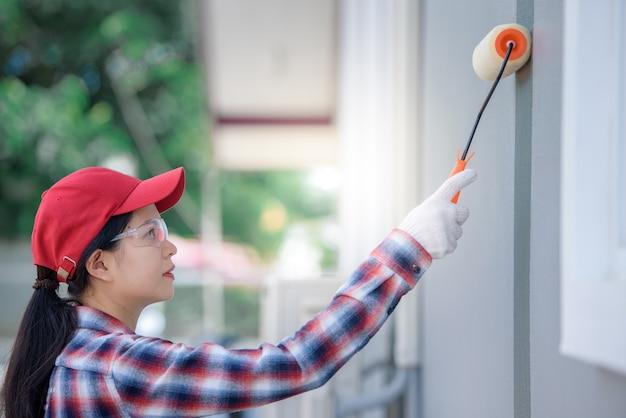 손으로 집의 젊은 아시아 여성 노동자 그림 벽과 회색 또는 시멘트 페인트 페인트 롤러 브러시 페인트