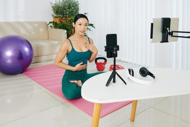그녀의 블로그에 운동 비디오를 녹화하는 젊은 아시아 피트니스 블로거