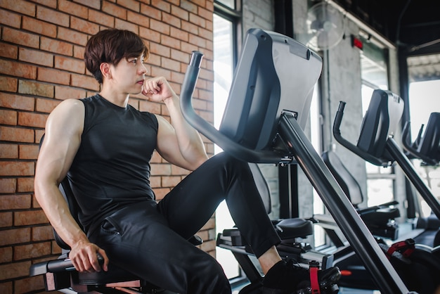 A young asian fitness trainer sitting at a gym equipment in the gym is responsible for recommending people to exercise.