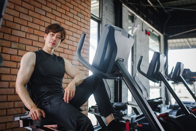 A young asian fitness trainer sitting at a gym