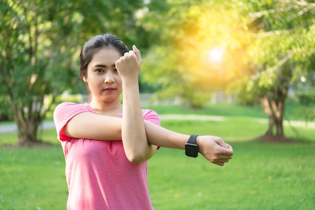 Young asian fitness woman stretching arms, tricep and shoulders before exercise in park.