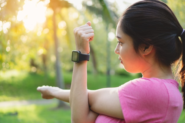 Young asian fitness woman wear smartwatch stretching arms, before exercise in park.