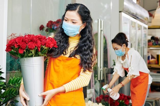 彼女の手で新鮮な赤いバラのバケツを見ている医療マスクの若いアジアの花屋