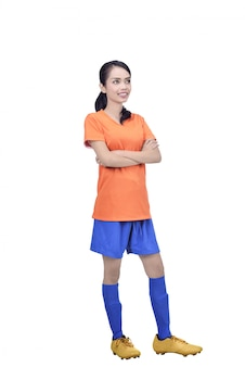 Young asian football player in orange jersey standing