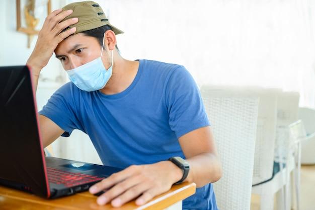의료용 마스크를 쓴 젊은 아시아 프리랜서 앉아서 온라인으로 입사 지원 결과를 봅니다.