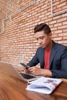 若いアジアフリーランサーのラップトップで座っていると、スマートフォンをチェック