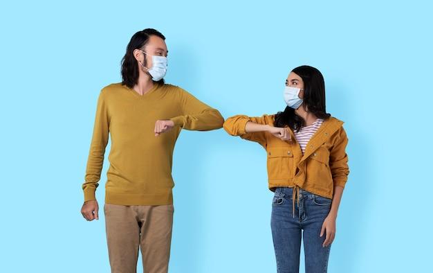 肘で挨拶する若いアジア人の友人。コロナウイルス(covid-19)の蔓延を避けるための新しい挨拶方法。