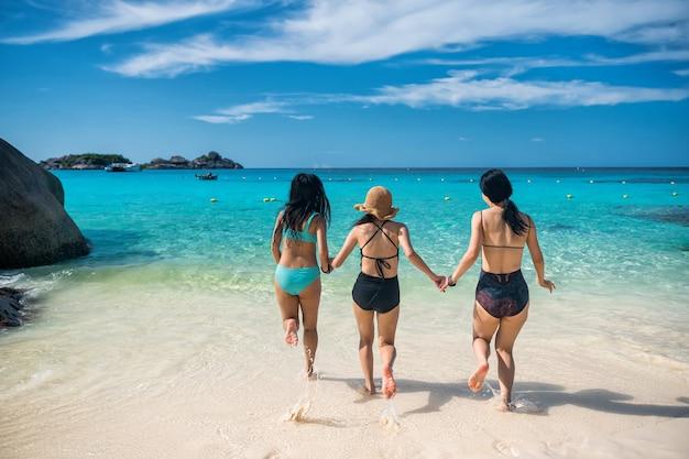 Молодые азиатские друзья сталкиваются с бирюзовым морем с голубым небом на пляже симиланского острова, пханг нга, таиланд. группа в составе создатель каникул праздника девушек в теплой стране