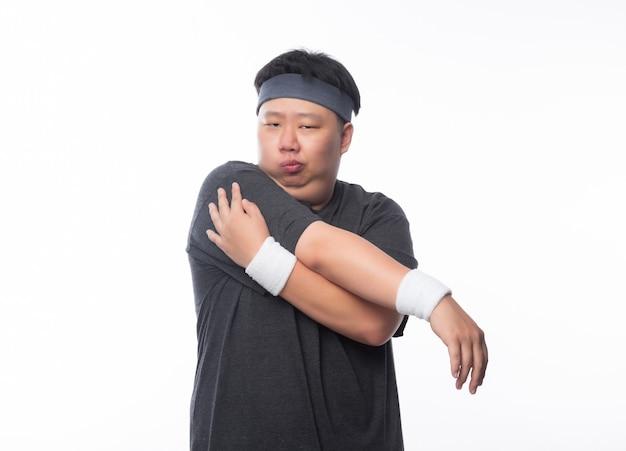 Молодой азиатский смешной тучный человек спорта протягивая перед изолированной тренировкой