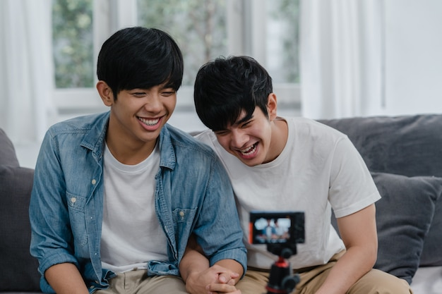 Young asian gay couple influencer couple vlog at home. teen korean lgbtq men happy relax fun using camera record vlog video upload in social media while lying sofa in living room at house .