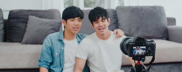 Young asian gay couple influencer couple vlog at home. teen korean lgbtq+ men happy relax fun using camera record vlog video upload in social media while lying sofa in living room at house .