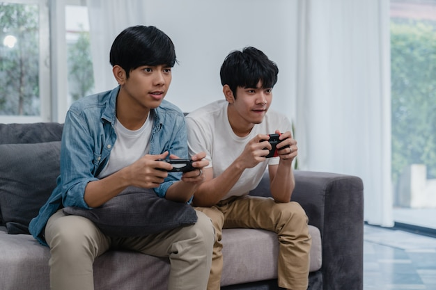 Young asian gay couple play games at home, teen korean lgbtq men using joystick having funny happy moment together on sofa in living room at house.