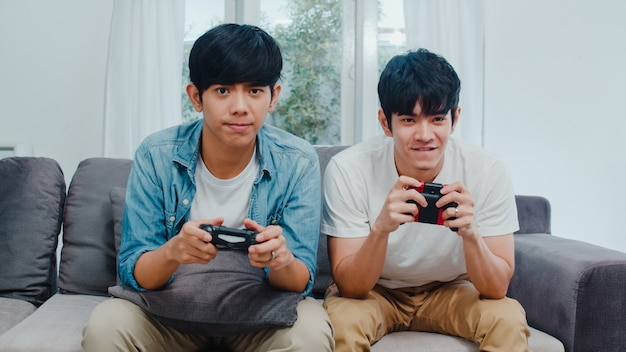 Young asian gay couple play games at home, teen korean lgbtq+ men using joystick having funny happy moment together on sofa in living room at house.