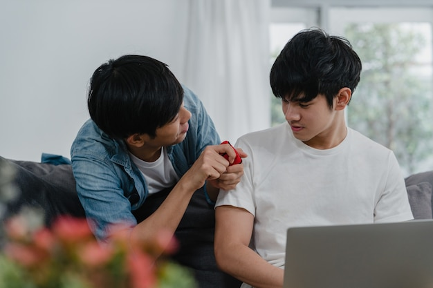 Young asian gay couple propose at modern home, teen korean lgbtq men happy smiling have romantic time while proposing and marriage surprise wear wedding ring in living room at house .