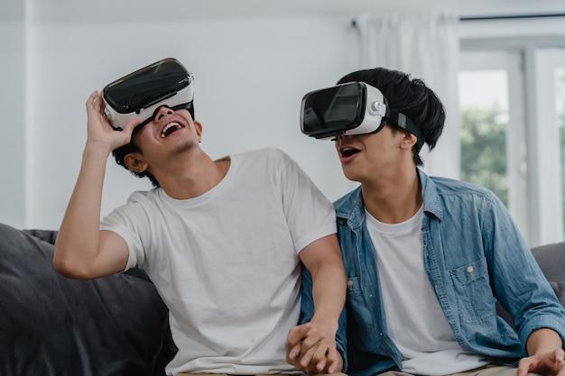 Молодая пара азиатских геев, использующих технологии, смешные дома, парень-любитель азии lgbtq +, чувствующий себя счастливым в виртуальной реальности, играющий в игры вместе, лежа на диване в гостиной дома.
