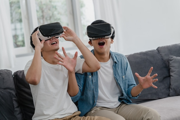 Young asian gay couple using technology funny at home, asia lover guy lgbtq+ feeling happy fun and virtual reality, vr playing games together while lying sofa in living room at home .