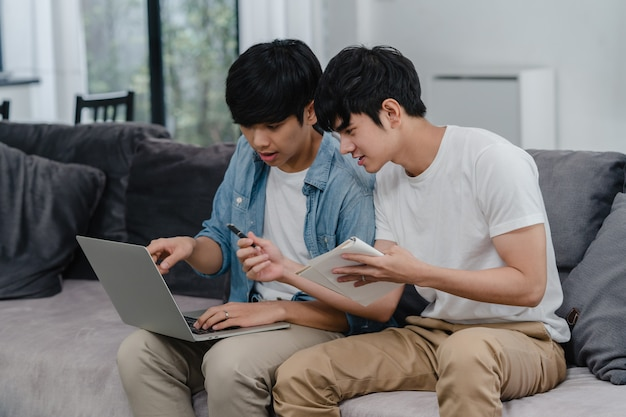 Young asian gay couple working laptop at modern home. asia lgbtq+ men happy relax fun using computer and analyzing their finances in internet together while lying sofa in living room at house .