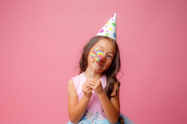 ピンクのロリポップの誕生日パーティーで若いアジアの女の子
