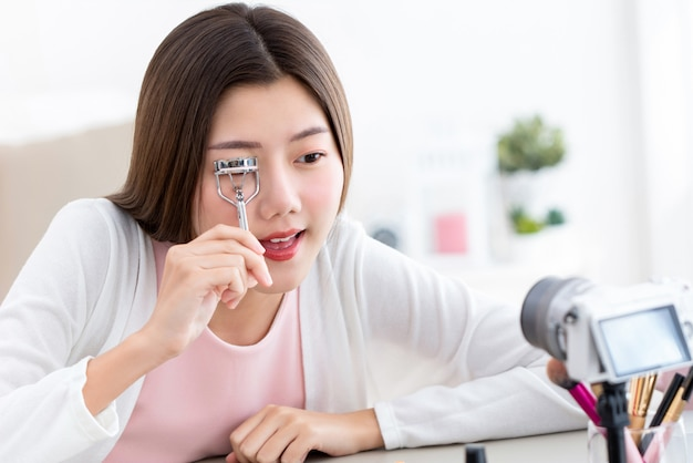 Young asian girl beauty vlogger testing new eyelash curler and recording video with camera at home