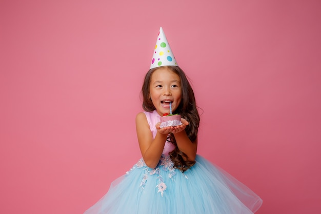 A young asian girl at a birthday party holds a cake with a candle on a pink