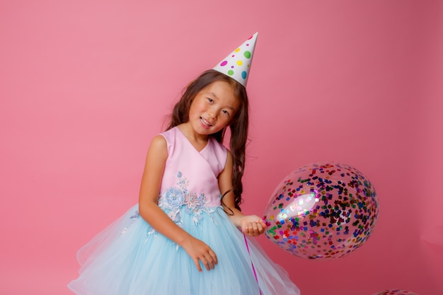 A young asian girl at a birthday party is playing with balloons on a pink