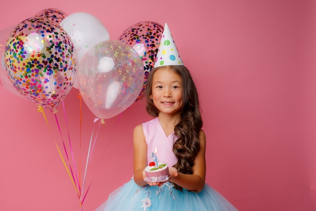 A young asian girl blows out a candle on a pink  at a birthday party