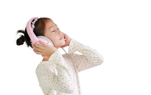 Молодые азиатские девочки, наслаждаясь с наушниками, слушая музыку, изолированные на белом фоне.