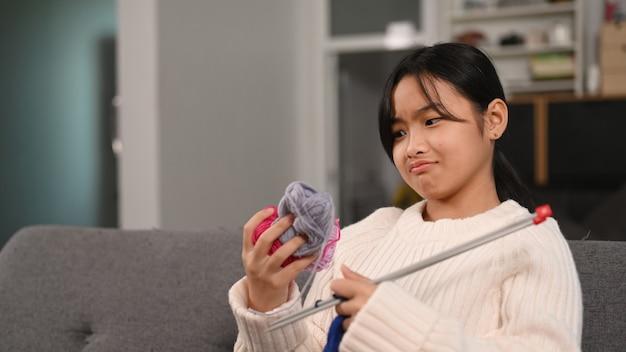 거실에 있는 소파에 앉아 뜨개질을 하기 위해 털실의 색을 선택하는 젊은 아시아 소녀. 공예 취미 개념입니다.