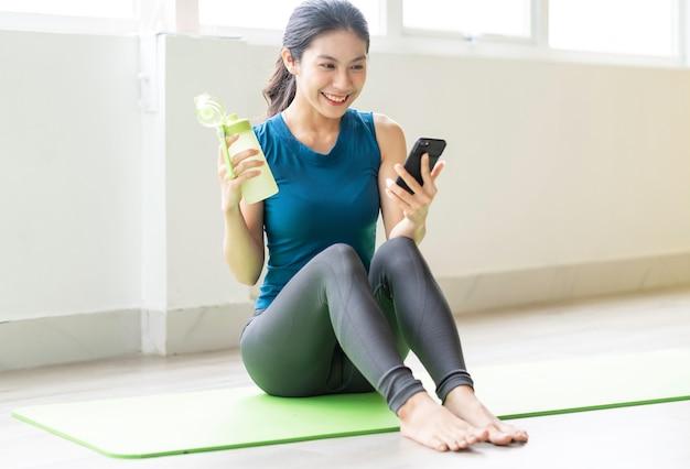 一人で床で運動をしている若いアジアの女の子