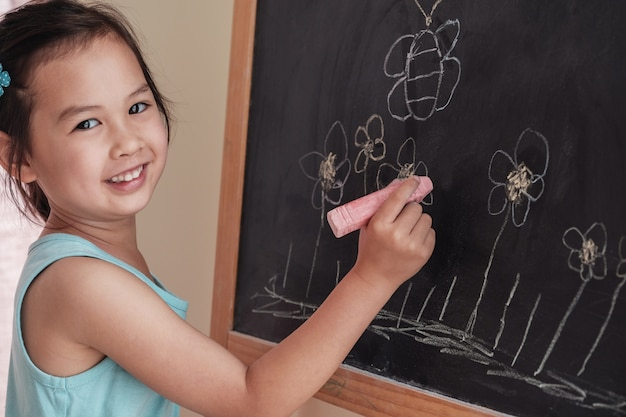 Young asian girl drawing on chalkboard, montessori homeschool education