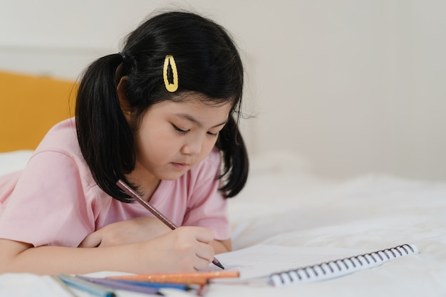Young asian girl drawing at home. asia japanese woman child kid relax rest fun happy draw cartoon in sketchbook before sleep lying on bed, feel comfort and calm in bedroom at night concept.
