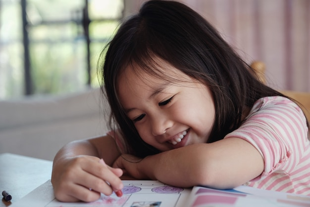 Young asian girl drawing at home, homeschool education