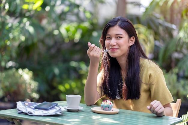 정원에서 뜨거운 커피와 먹고 먹고 젊은 아시아 소녀