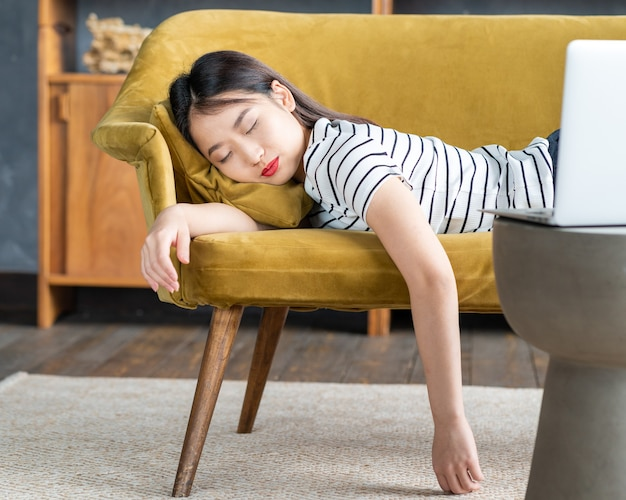 Young asian girl fell asleep oncouch in front oflaptop. cute woman is bored, tired or overworked. cozy home environment, soft sofa