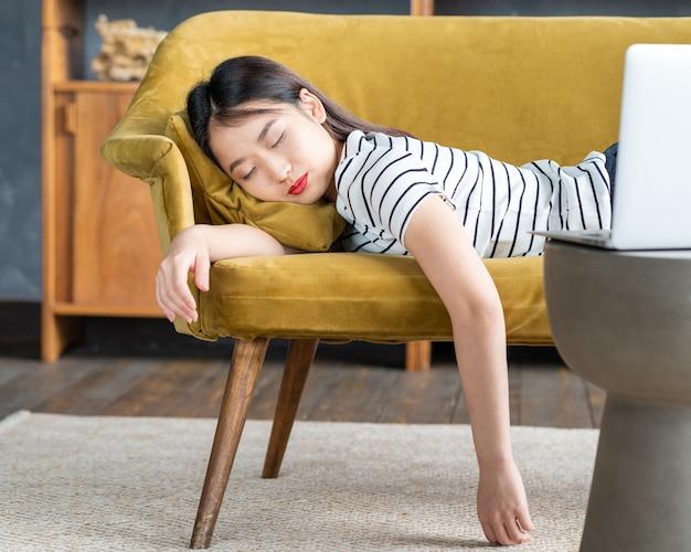 Молодая азиатская девушка заснула на диване перед ноутбуком. симпатичной женщине скучно, она устала или перегружена. уютная домашняя обстановка, мягкий диван