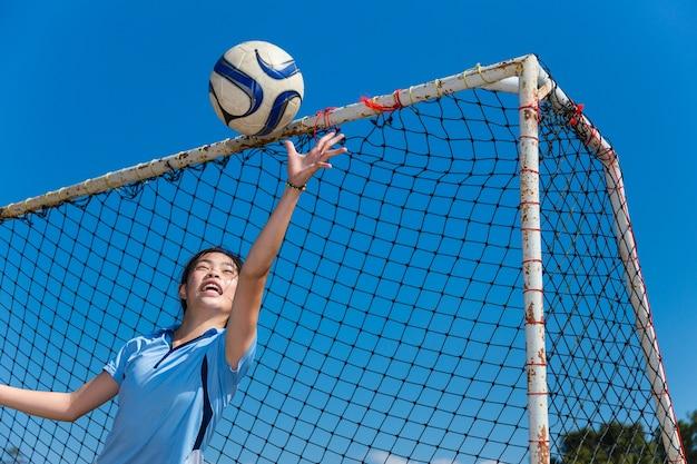 若いアジアの女の子のゴールキーパーボールをキャッチ