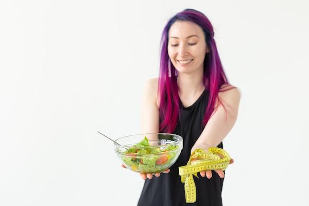 若いアジアの女の子の流行に敏感な色の髪は、白い壁にポーズをとってメジャーテープと野菜のサラダを手に持っています。健康的な食事の概念。