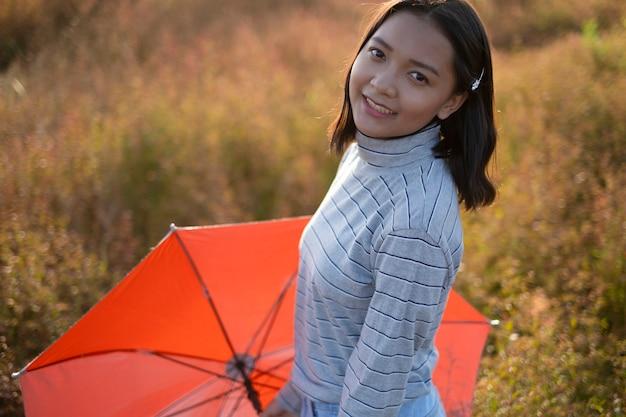 若いアジアの女の子はオレンジ色の傘を持って、茶色の野草に微笑んでいます。