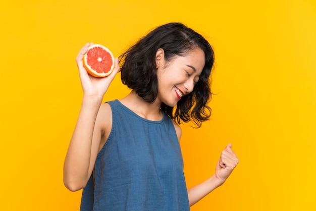 Молодая азиатская девушка держа грейпфрут над изолированной оранжевой предпосылкой празднуя победу