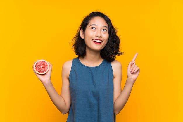 Молодая азиатская девушка держа грейпфрут над изолированной оранжевой предпосылкой указывая вверх по отличной идее