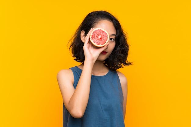 Молодая азиатская девушка держа грейпфрут над изолированной оранжевой предпосылкой