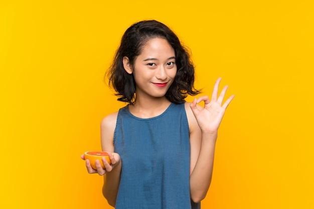 Молодая азиатская девушка держа грейпфрут